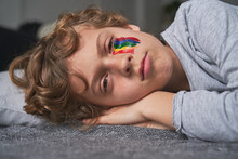 Sad Boy With Bright Rainbow Under Eye Lying On Pillow And Blanket And Looking At Camera While Staying Home During Quarantine