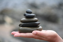 Cropped Hand Holding Stacked Pebbles