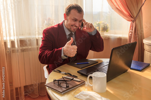 Remote work, Sitting at the kitchen table, a young man in a business suit and sh Canvas Print
