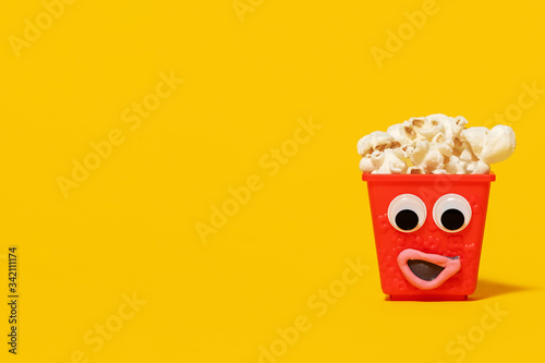 Photo Mini red popcorn carton box with googly eyes and a goofy smiling expression full of popcorn on a yellow background with copy space and room for text with a right side composition