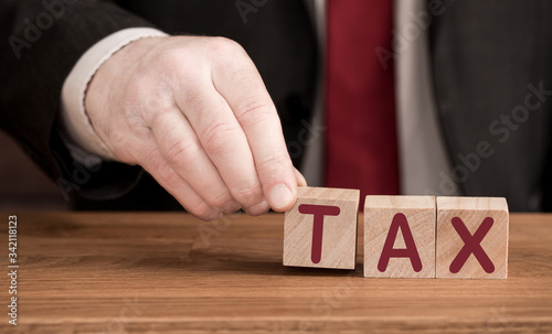 A TAX concept with a businessman or accountant creating the acronym TAX in woode Canvas Print