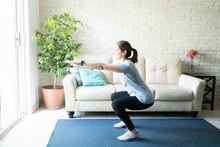 Active Woman Doing Squats At H...