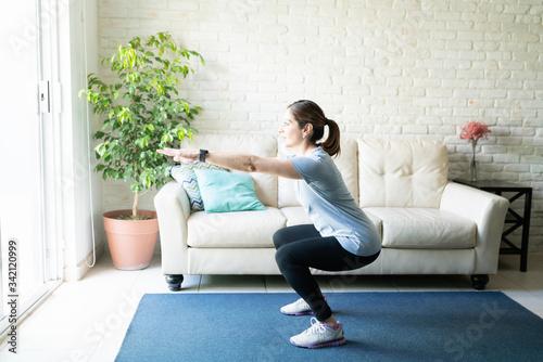 Fototapeta Active woman doing squats at home obraz