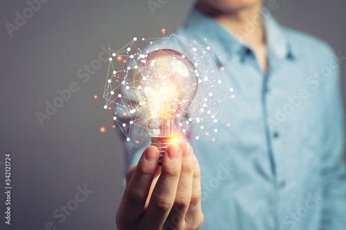 Man holding light bulbs, ideas of new ideas with innovative technology and creativity Wallpaper Mural