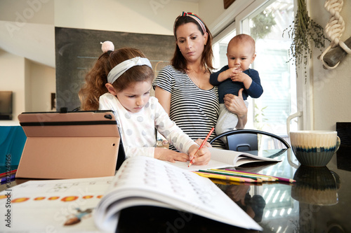 A mother holding a baby homeschools her daughter Canvas-taulu