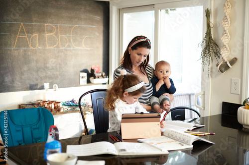 Vászonkép A mother with a baby boy homeschools her daughter