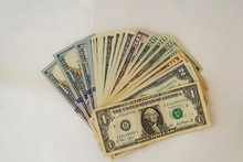 Several Hundred Dollar Bills Fanned Out On White Background