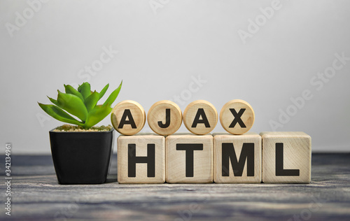 AJAX HTML - text on wooden cubes, green plant in black pot on a wooden backgroun Wallpaper Mural