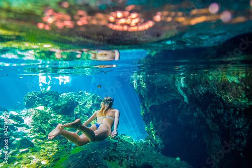 Fototapeta A woman snorkels in crystal blue water obraz
