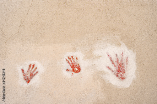 Vászonkép Red handprints on the wall