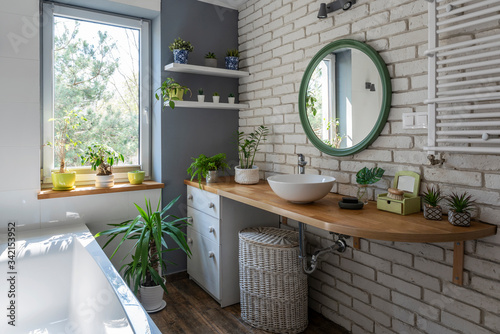 Industrial white bathroom with window, bath, brick wall, green plants and wooden counter. Loft interior of bathroom in apartment in scandinavian style.