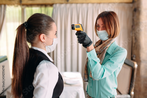 Foto The Manager of a restaurant or hotel checks the body temperature of the staff with a thermal imaging device