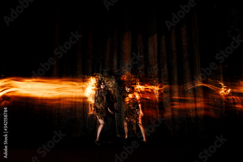 Photo Ghost girls, spirits of the theater, accompanied by a trail of fire, on the stage of the theater