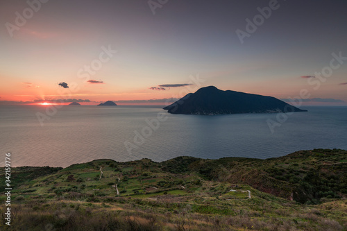 Coast with grass fields of Lipari with view to volcano islands Salina, Alicudi, Filicudi during sunset, Sicily Italy Canvas Print