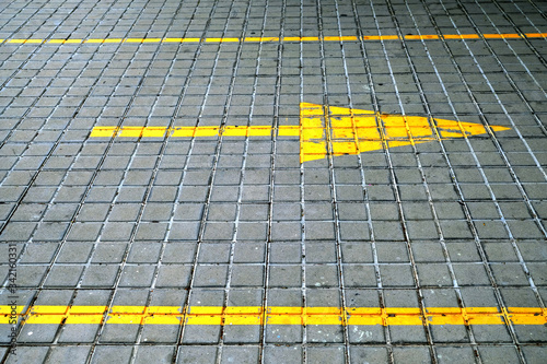 A yellow arrow pointing right in yellow paint on gray concrete blocks pavement Wallpaper Mural