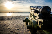 Old Cannon At Harbor Against Sky During Sunset