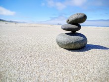 Stack Of Stones On Sand At Beach Against Sky