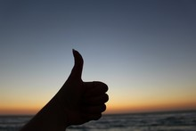 Silhouette Cropped Hand Gesturing Thumbs Up On Shore During Sunset