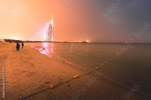 Платно Burj al Arab and Jumeirah beach at dusk Dubai - UAE