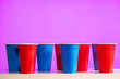 canvas print picture - Disposable red and blue plastic party beer cups on a white table or shelf with a bright modern purple background.
