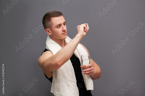 Photo Man takes a pill of amino acids after training.