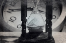 Close-up Of Hourglass Against Clock