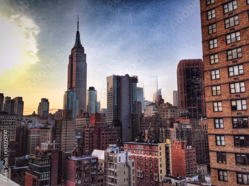 Платно Empire State Building In City Against Sky At Sunset