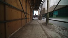 Walking Through Long Empty Construction Alley Scaffolding