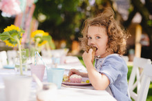 Small Girl Sitting Outdoors In Garden In Summer, Eating Snacks.