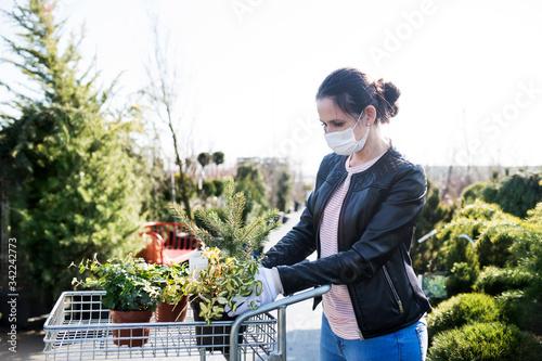 Obraz Young woman with face mask outdoors shopping in garden center, Corona virus concept. - fototapety do salonu
