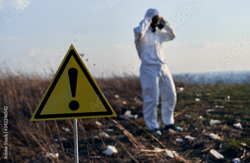 Yellow warning sign about danger and hazards in field with trash Canvas-taulu