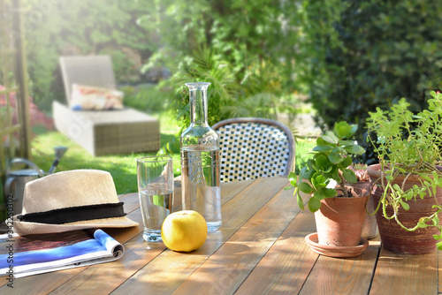 close on drink glass and apple on a wooden table in garden background in summer