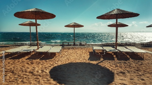 Fotografiet Parasol By Deck Chair On Sand At Beach Against Sky
