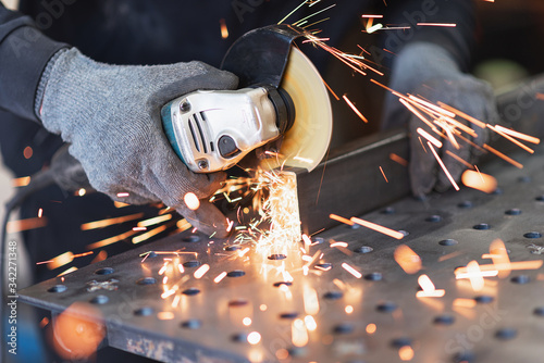 A metal worker cuts a rectangular metal pipe with an angle grinder Tableau sur Toile