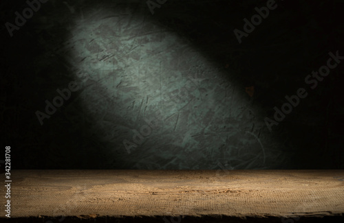 Old wood table with blurred concrete block wall in dark room background Canvas Print