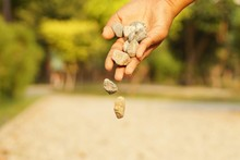Cropped Image Of Hand Throwing Stones On Field