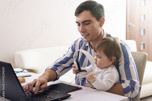 dark-haired man in striped shirt with baby on lap, remote work in quarantine, li Tablou Canvas