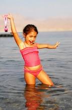 Portrait Of Happy Girl Wearing Swimwear Dancing In River