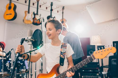 Photo kids rock band practice in music studio