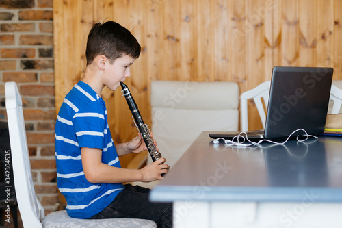 Boy with a clarinet plays music. Online music lesson concept Canvas Print