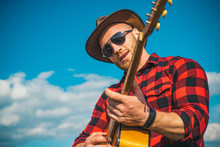Man With Guitar. Handsome Young Man Wearing Sunglasses And Playing Guitar On Sky Background. Cowboy Men. Western Camping.