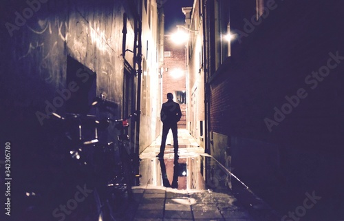 Silhouette Person Standing On Wet Road Amidst Buildings At Night Wallpaper Mural