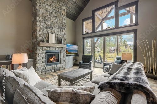 Fotografia Living room luxury interior with large stone fireplace and leather furniture and huge tall windows with natural tones