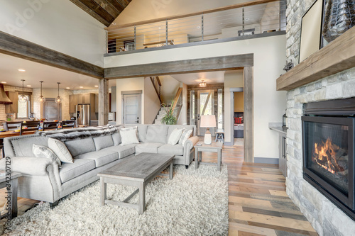 Fotografia Living room luxury interior with large stone fireplace and leather furniture and huge tall windows with natural tones with TV