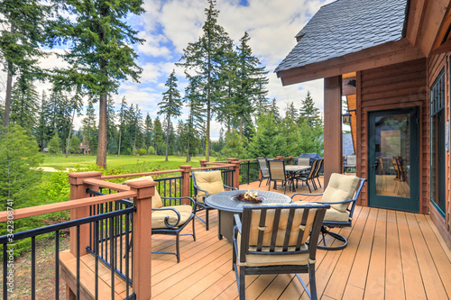 Photo Beautiful large cabin home  with large wooden deck and chairs with table overlooking golf course