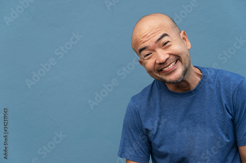 40s of smiling funny Japanese portrait man in t-shirt on blue cement background Wallpaper Mural
