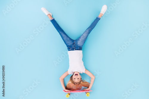Top above high angle view full body photo of positive girl sporty kid ride longboard upside down show tongue out wear white clothes lay isolated over blue color background