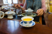 Porcelain Tea Cup With Beautiful Blue Patterns. Filled With Pu Erh Tea, Gung Fu Cha Style. Blurred Background.
