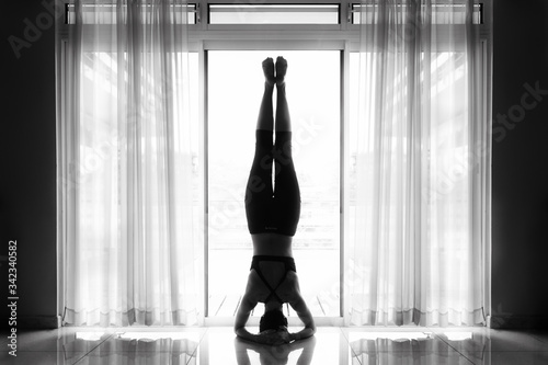 Valokuva Rear View Woman Doing Yoga On Floor By Window At Home