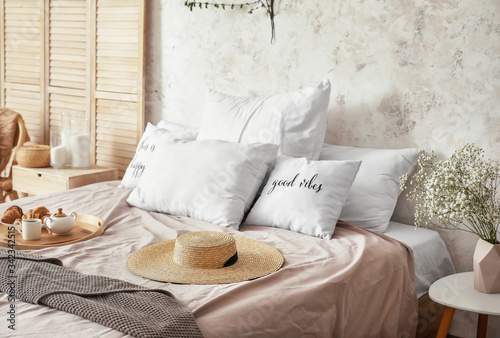 Interior of beautiful modern bedroom with breakfast and spring flowers